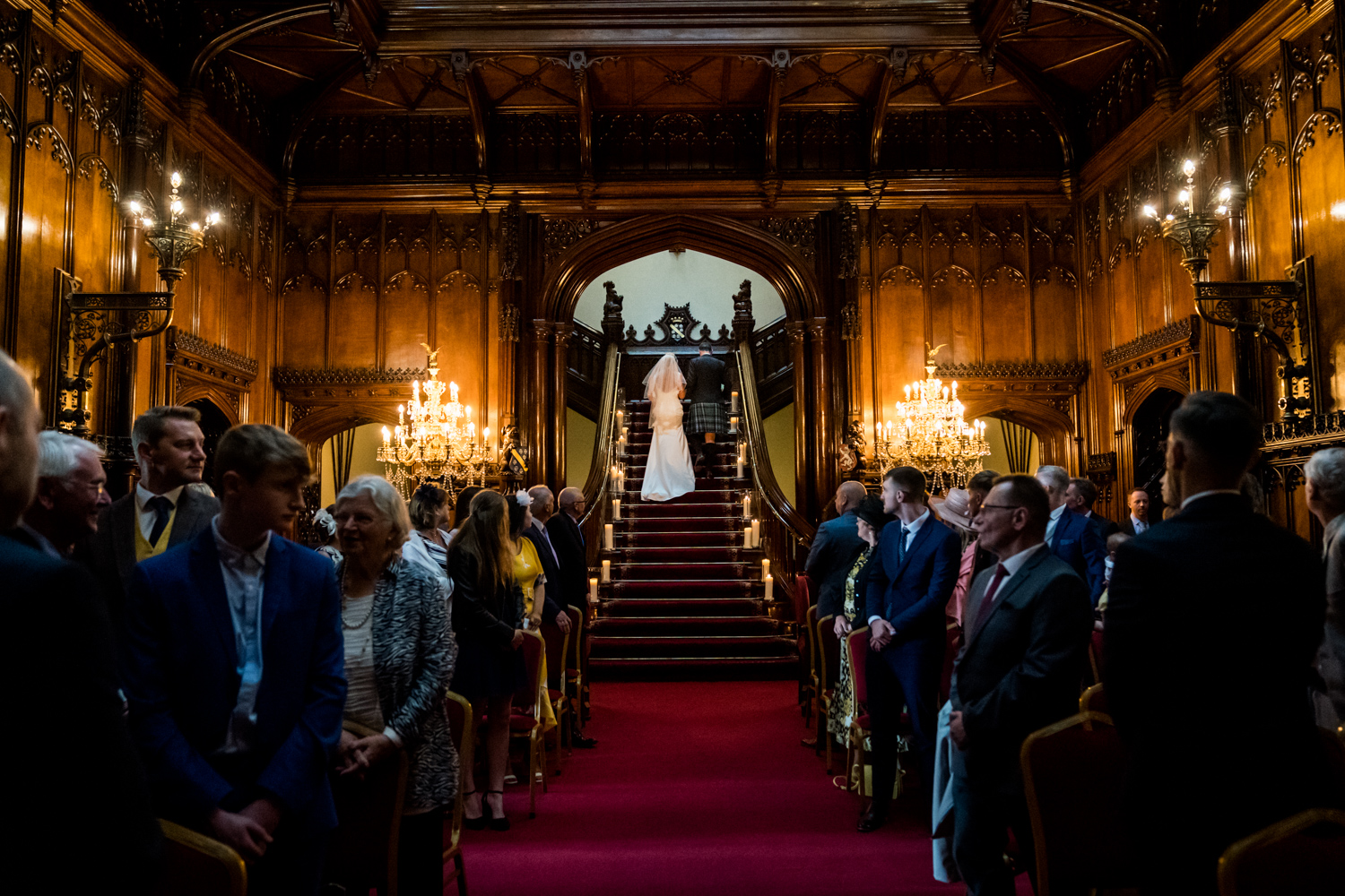 Allerton Castle Wedding Photography - couple leaving the ceremony via the grand staircase