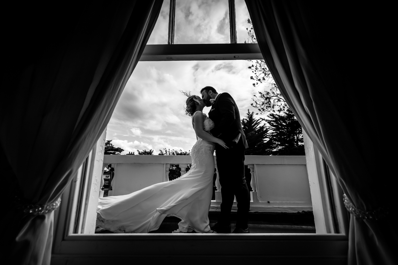 Dunedin House Wedding Photography - couple kissing on the balcony